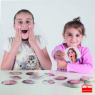 """Die 10 Emotionen erkennen - zwei Kinder, die das Spiel spielen - eines hält die Karte """"überrascht"""" hoch, das andere Kind spielt die Emotion nach."""