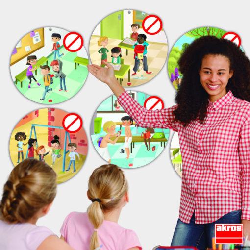 Eine Schwarze Lehrerin steht in erklärender Pose vor den Anti-Mobbing Postern. Sie redet mit zwei Kindern über eine der Situationen auf den Postern.