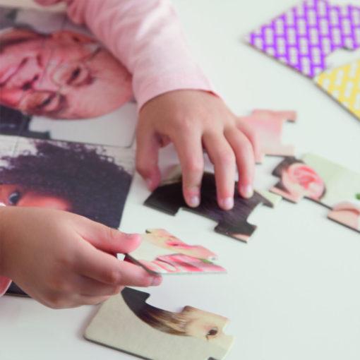 Eine Kinderhand puzzelt ein Puzzle als Beispiel für eine Anwendung. Die Puzzleteile sind groß und können gut gegriffen werden.