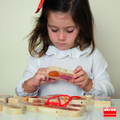 Ein Kind schaut sich eine der Figuren aus dem Set Fädelspiel Familien genauer an. Das Kind ist sehr vertieft in seine Tätigkeit.