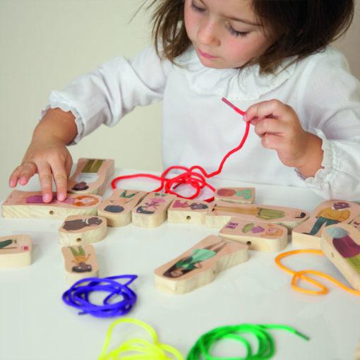 Ein Kind sitzt an einem Tisch und schaut sich die verschiedenen Figuren aus dem Set an. In der Hand hält es eine rote Fädelschnur. Das Ende der Schnur ist wie bei einem Schnürsenkel ummantelt - für leichtes Auffädeln.
