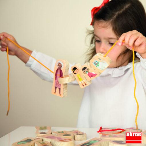 Ein Kind hält einen gelben Faden hoch auf das es 5 unterschiedliche Figuren aufgefädelt hat.