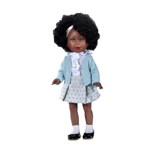 Schwarze Puppe Paulina 835 (mit brauner Hautfarbe) und Afro. Weißes Satin- Haarband, passend zur weißen Bluse und den weißen Söckchen. Knielanger hellblauer Rock mit Muster und hellblaue Strickjacke, schwarze Lackballerinas. Fester Körper.