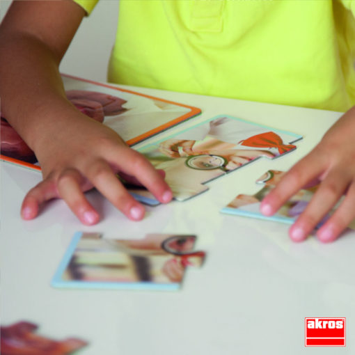 Zwei Hände, die gerade ein Puzzle zusammenlegen. Auf dem Puzzle ist ein weißes Kind mit großer schwarzer Brille zu sehen.