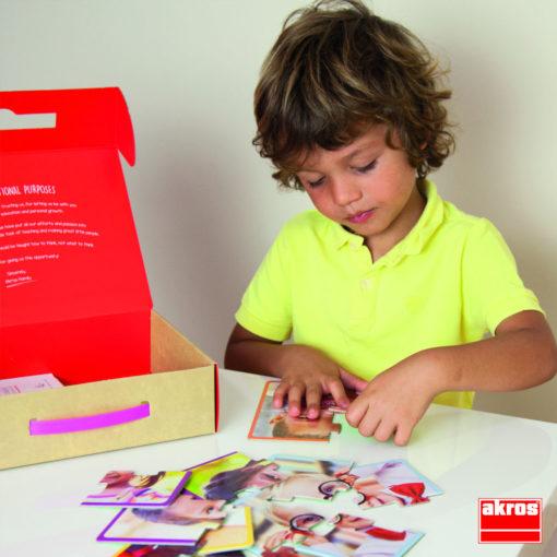 Ein Kind sitzt an einem Tisch. Vor ihm liegen Puzzleteile. Das Kind puzzelt eines der großformatigen Puzzles Kinder der Welt von akros
