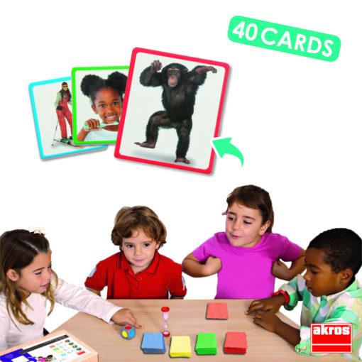 """Eine Gruppe von 4 Kindern spielt das Spiel """"Was bin ich?"""" Als Beispielkarten sind ein Affe, ein Kind das Zähne putzt und eine Skifahrerin gezeigt. Es gibt 40 Karten, eine Sanduhr und einen großen Würfel."""