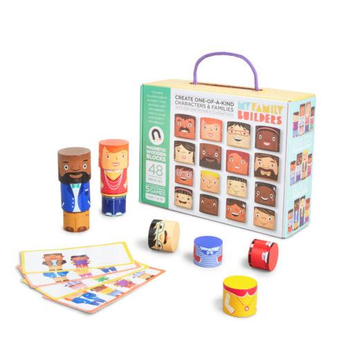 Karton My Family Builders - friend editon mit 48 magnetischen runden Holzklötzen, aus denen Figuren gebaut werden können. Einige Beispielfiguren und Spielkarten sind vor dem Karton zu sehen. Die abgebildeten Köpfe zeigen verschiedene Hautfarben, Haarfarben, unterschiedliches Alter, männliche, weibliche und eher androgyne gelesene Köpfe.