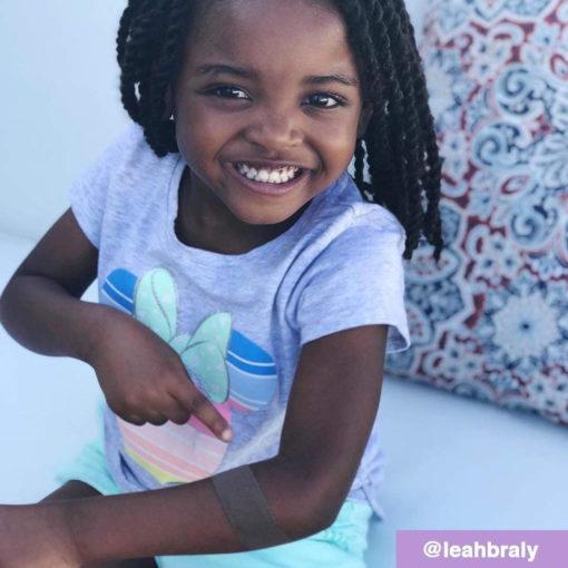 Schwarzes Mädchen lacht in die Kamera und zeigt auf ein dunkelbraunes Pflaster am Arm, das man kaum sehen kann