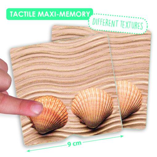 """Ein Finger streicht über die Memorykarte """"Muscheln"""" des taktilen Memorys. Die Kartengröße ist mit 9 x 9cm markiert. Hinweistext: verschiedene Texturen."""