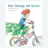 Buchcover Der Junge im Rock - ein Junge im geblümten Rock, blauem T-Shirt, rotem Fahrradhelm auf einem Mountainbike