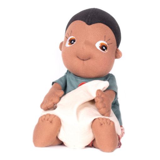 Rubens Barn Tummies Puppe Kevin: Schwarze Puppe mit gestreifter Hose und blaugrauem Shirt, hält ein Körnerkissen im Arm