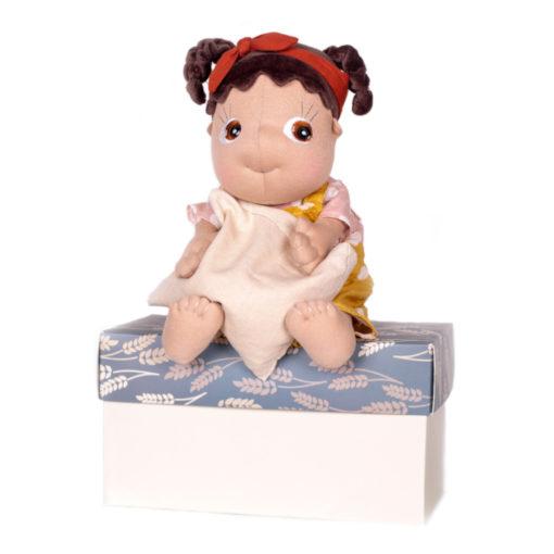 Rubens Barn Tummies Puppe Lumi: PoC Puppe mit Körnerkissen im Arm auf Box sitzend
