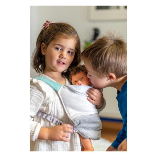 Kind mit Down Syndrom und Kind ohne Down-Syndrom spielen mit Puppe mit Down Syndrom