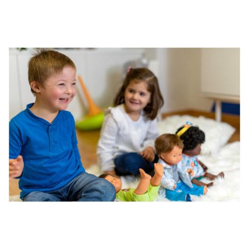 Kind mit Down Syndrom und Kind ohne Down-Syndrom spielen mit Puppen mit und ohne Down Syndrom