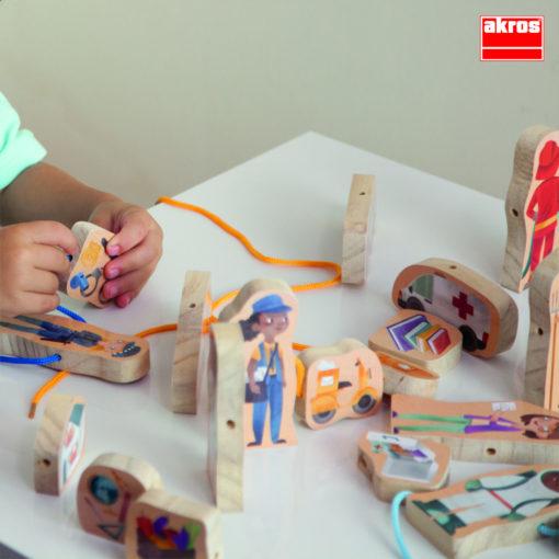 Kinderhände greifen eine der Holzfiguren und fädeln gerade die Schnur hindurch. Auf der Tischplatte sind einige Figuren verteilt.