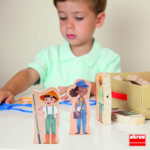 Im Hintergrund schaut ein Kind auf die Schnüre des Fädelspiels. Im Vordergrund sind die Figuren des Anglers und der Postbotin zu sehen.