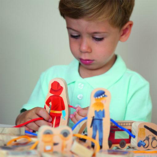 Ein Kind ist im Spiel versunken und fädelt eine rote Schnur durch die Figur des Feuerwehrmanns. Im Vordergrund liegen und stehen weitere Figuren.